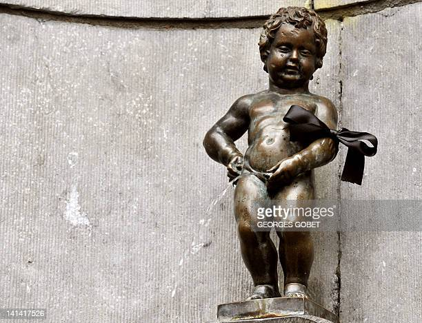 The Belgian statue Manneken pis wears a black arm band on March 16 2012 Belgium observes a national day of mourning for the victims of the March 13...