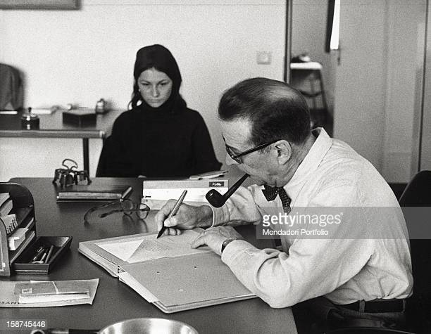 The Belgian writer Georges Simenon writing a letter smoking a pipe Epalinges 1966