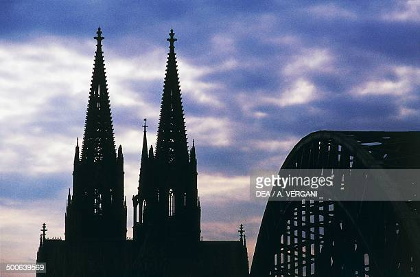 The bell towers of Cologne Cathedral and the Hohenzollern Bridge on the Rhine river Germany