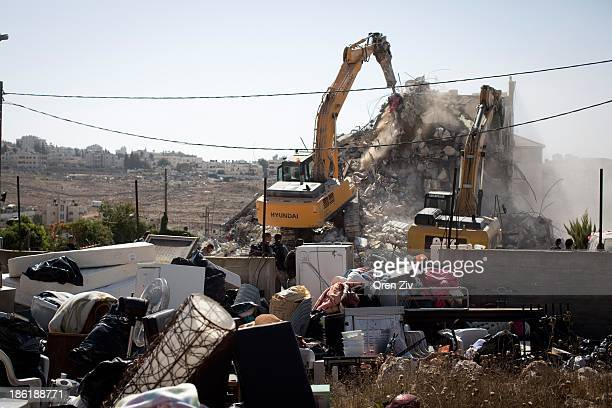 The belongings of a Palestinian family lie in the open as Jerusalem municipality workers use bulldozers to demolish a residential building in an East...