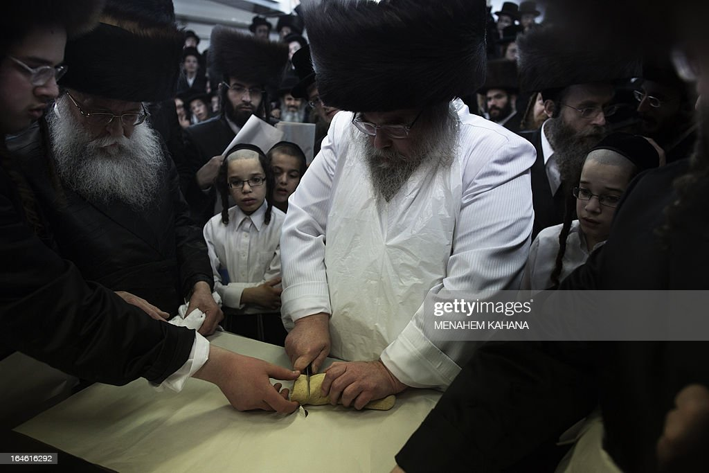 The Belz rabbi cuts the dough before baking the matzoth or unleavened bread for the Pesach holiday (Passover) in Jerusalem on March 25, 2013. Religious Jews throughout the world eat matzoth during the eight-day Pesach holiday (Passover), which begins on March 25 at sunset and commemorates the Israelites' exodus from slavery in Egypt some 3,500 years ago and their plight by refraining from eating leavened food products.