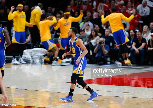 The bench players of the Golden State Warriors celebrate a three point shot by Stephen Curry against the Portland Trail Blazers during Game Four of...