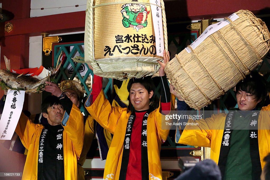 The best 'Fuku otoko' or lucky man', Yuto Doi (C) poses for photographs after winning the 'Lucky Man' race as a part of the 'Toka Ebisu' festival at Nishinomiya Shrine on January 10, 2013 in Nishinomiya, Hyogo, Japan. The annual race, start at 6:00am on Janaury 10, competed by running 230 meters from the gate to the main hall.