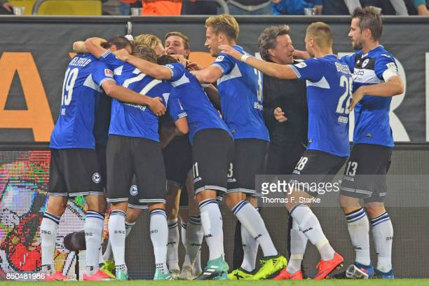The Bielefeld team celebrates with head coach Jeff Saibene during the Second Bundesliga match between SG Dynamo Dresden and DSC Arminia Bielefeld at...