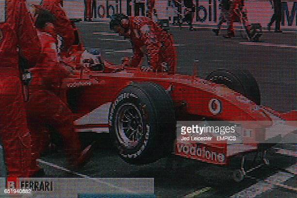 The big screen Tv shows Ferrari's Rubens Barrichello making his pit stop during the race