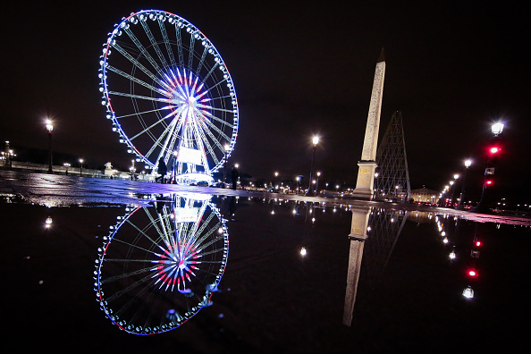 The Big Wheel and the Luxor Obelisk reflecting into a puddle on Place de La Concorde on February 4 2016 in Paris France