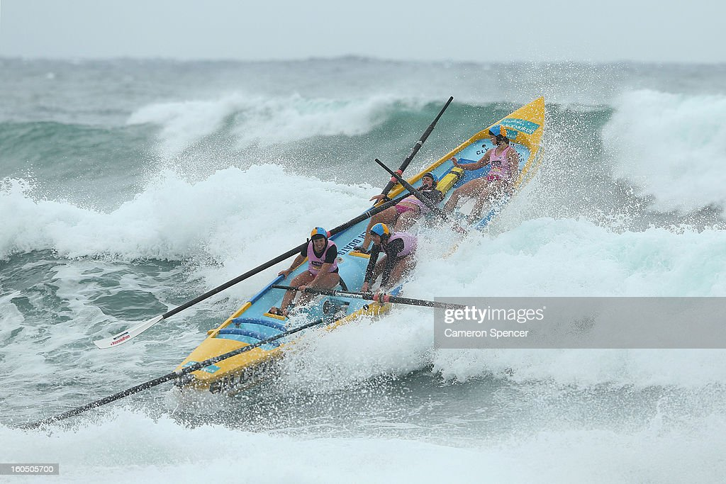 The Bilgola womens suf life saving crew paddle through a wave during the Ocean Thunder Surf Boat Series at Dee Why Beach on February 2, 2013 in Sydney, Australia.