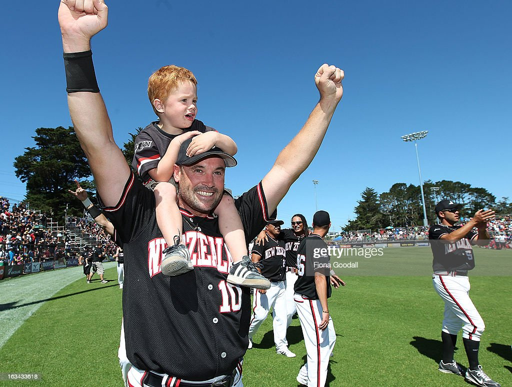 The Black Sox captain Rhys Casley and his son celebrate winning the Softball World Championship over Venezuela at Tradstaff Sports Stadium on March 10, 2013 in Auckland, New Zealand.