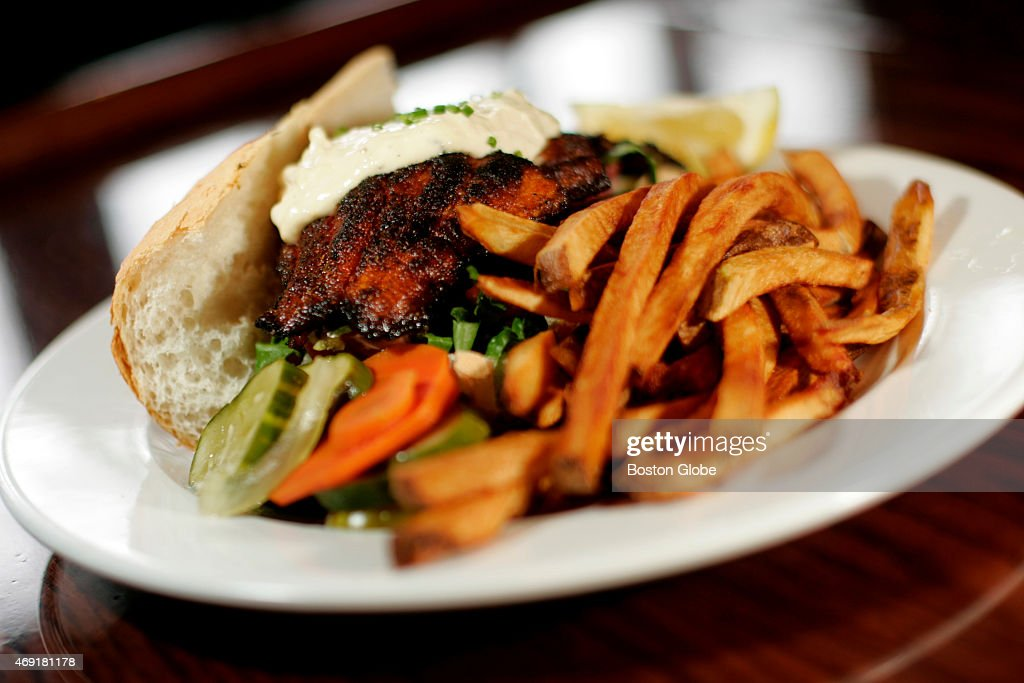 The blackened catfish po' boy with remoulade shredded lettuce tomatoes and pickles on french bread at Highland Kitchen in Somerville Mass