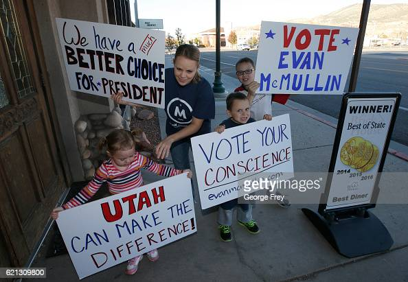 The Blodtett family sets up signs at the Brick House Cafe for a rally for US independent presidential candidate Evan McMullin on November 5 2016 in...