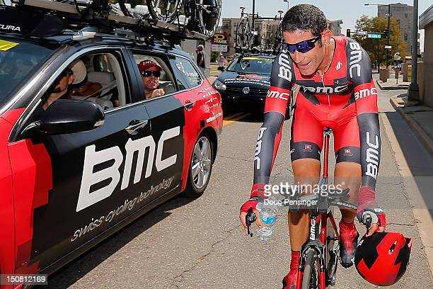 The BMC Racing team car with Cadel Evans of Australia in the back seat congratulate George Hincapie of the USA riding for BMC Racing after he...