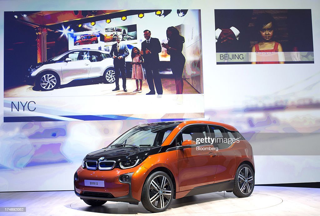 The BMW i3, the electric automobile produced by Bayerische Motoren Werke AG (BMW), is seen on the stage in London during the simultaneous world premiere, with live video links from New York and Beijing, in London, U.K., on Monday, July 29, 2013. To avoid the fate of other slow-selling electric vehicles, Bayerische Motoren Werke AG will offer the new i3 -- a battery-powered compact car -- with a unique option: the use of a sport-utility vehicle. Photographer: Simon Dawson/Bloomberg via Getty Images