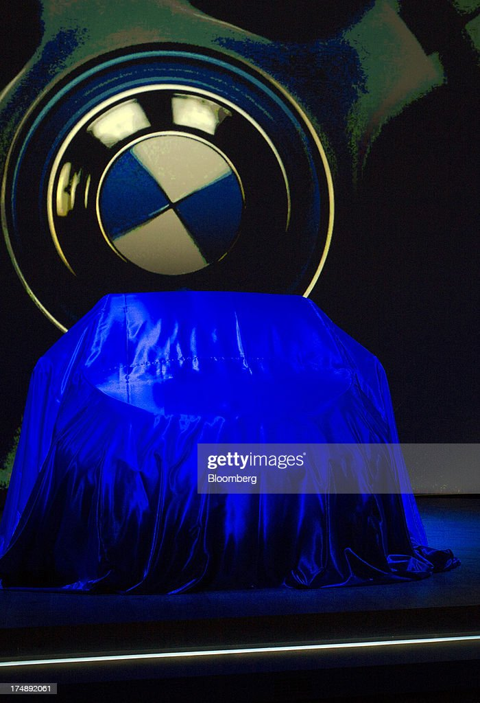 The BMW i3, the electric automobile produced by Bayerische Motoren Werke AG (BMW), sits on the stage covered by a blue cloth prior to being unveiled at the world premiere launch in London, U.K., on Monday, July 29, 2013. To avoid the fate of other slow-selling electric vehicles, Bayerische Motoren Werke AG will offer the new i3 -- a battery-powered compact car -- with a unique option: the use of a sport-utility vehicle. Photographer: Simon Dawson/Bloomberg via Getty Images