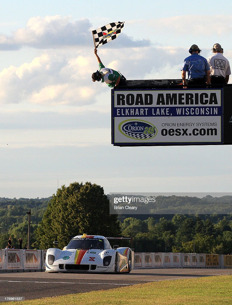 The #2 BMW Riley of Brendon Hartley of New Zealand and Scott Mayer takes the checkered flag to win the VisitFlorida.com Sports Car 250 at Road America on August 10, 2013 in Elkhart Lake, Wisconsin.