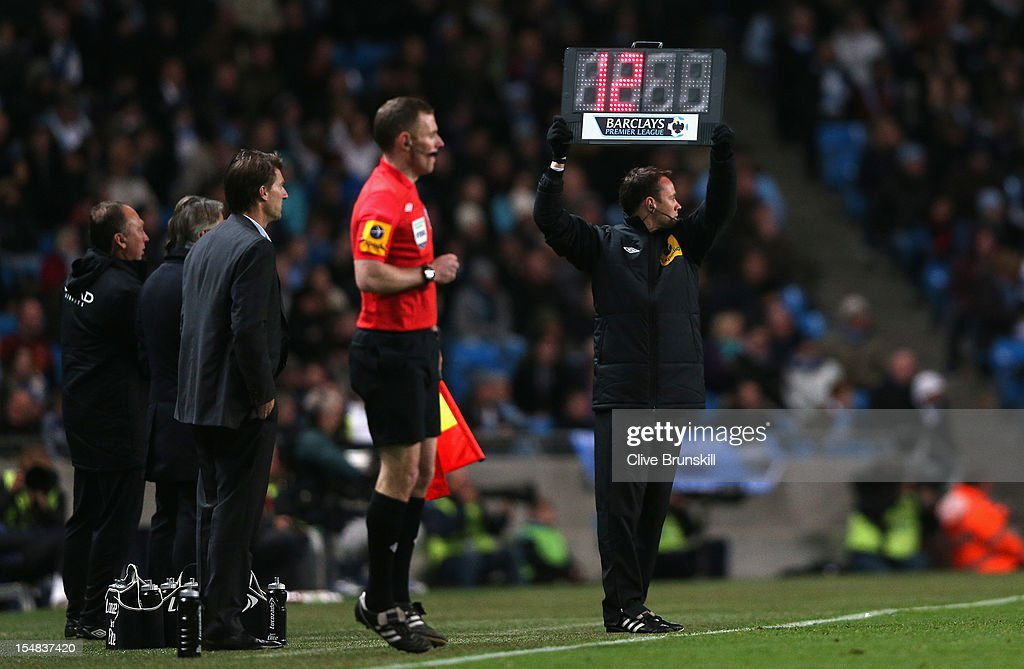 The board is held up by the Fourth Official showing 12 minutes of injury time to be played during the Barclays Premier League match between Manchester City and Swansea City at the Etihad Stadium on October 27, 2012 in Manchester, England.