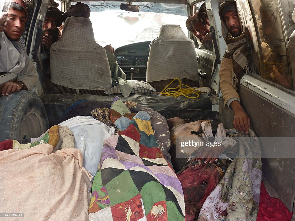 The bodies of Afghan civilians allegedly shot by a rogue US soldier are pictured in the back of a van in Alkozai village of Panjwayi district, Kandahar province on March 11, 2012. An AFP reporter counted 16 bodies -- including women and children -- in three Afghan houses after a rogue US soldier walked out of his base and began shooting civilians early Sunday. NATO's International Security Assistance Force said it had arrested a soldier 'in connection to an incident that resulted in Afghan casualties in Kandahar province', without giving a figure for the dead or wounded. AFP PHOTO/ MAMOON DURRANI