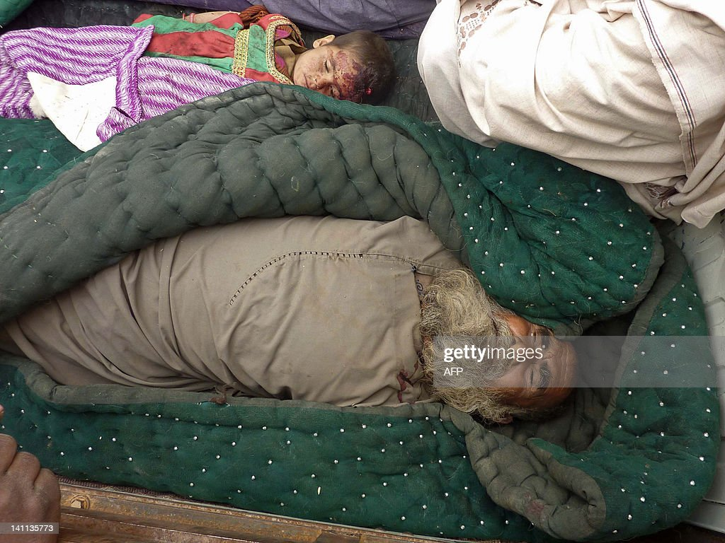 The bodies of an elderly Afghan man and a child are pictured in Alkozai village of Panjwayi district, Kandahar province on March 11, 2012. An AFP reporter counted 16 bodies -- including women and children -- in three Afghan houses after a rogue US soldier walked out of his base and began shooting civilians early Sunday. NATO's International Security Assistance Force said it had arrested a soldier 'in connection to an incident that resulted in Afghan casualties in Kandahar province', without giving a figure for the dead or wounded. AFP PHOTO/ MAMOON DURRANI