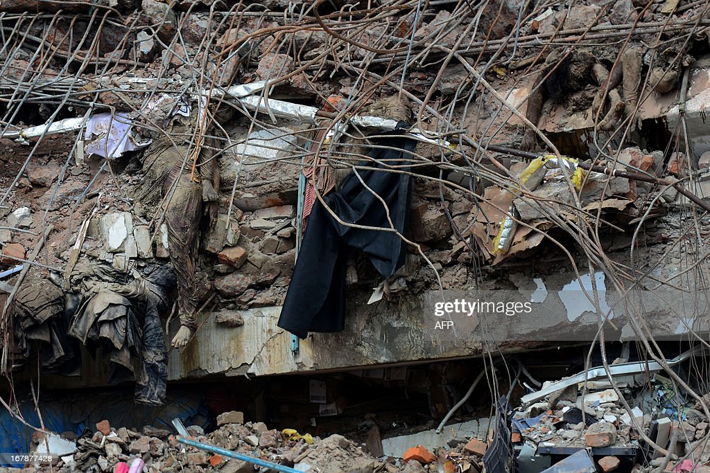The bodies of Bangladeshi garment workers lie crushed under rubble after an eight-storey building collapse in Savar, on the outskirts of Dhaka,on May 2, 2013. Bangladesh authorities have suspended the mayor of Savar satellite town outside the capital for approving the faulty construction of a building that collapsed last week, killing 429 people. AFP PHOTO/ Munir uz ZAMAN