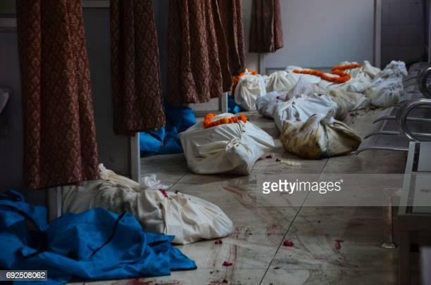 The bodies of bus passengers are left in bags on the ground in a district hospital in Bareilly in India's Uttar Pradesh state on June 5 2017 after a...