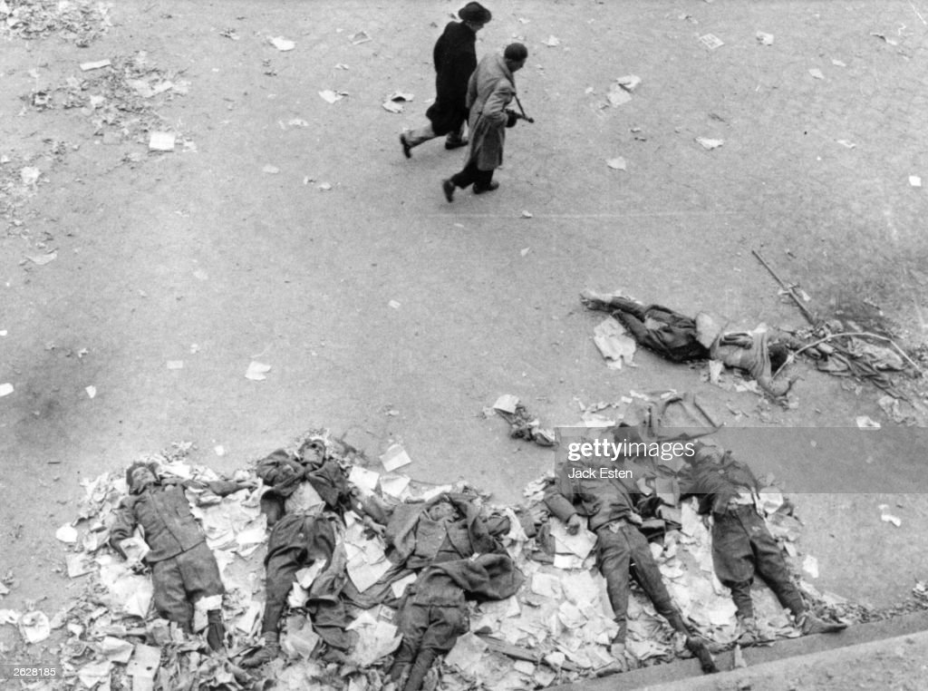 The bodies of Hungarian State Secret Policemen lie mutilated outside their old headquarters, strewn with unread Russian propaganda. Two patriot soldiers walk past with no apparent concern for their former oppressors. Original Publication: Picture Post - 8730 - Hungary's Last Battle For Freedom - pub. 1956