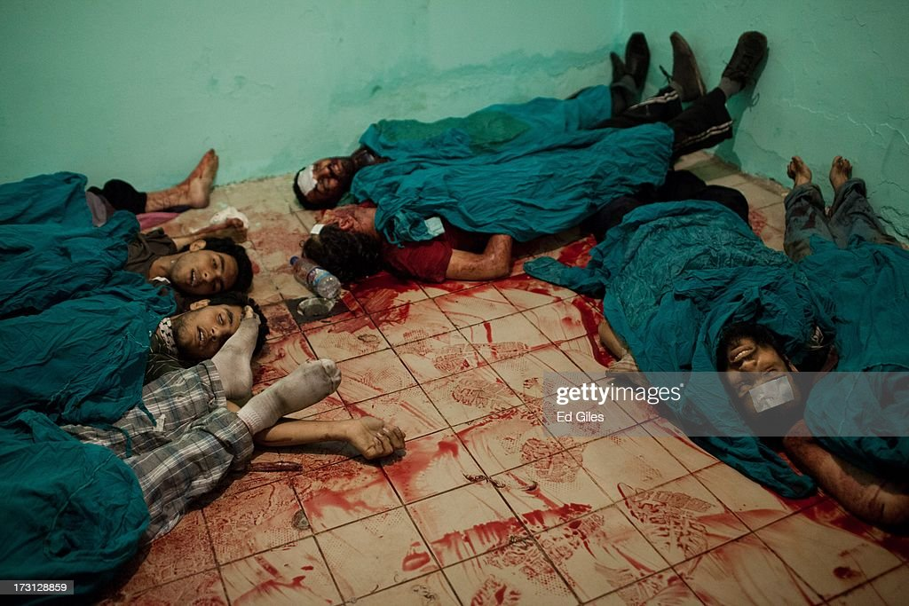 The bodies of men lie on the floor of a morgue at the Liltaqmeen al-Sahy Hospital in Cairo's Nasr City district, after allegedly being killed during a shooting at the site of a pro-Morsi sit-in in front of the headquarters of the Egyptian Republican Guard on July 8, 2013 in Cairo, Egypt. Egyptian health ministry officials are reporting at least 42 people were killed and more than 300 injured in the incident early on Monday morning, which allegedly occurred as supporters of deposed Egyptian President Mohammed Morsi attending the sit in were performing dawn prayer. The demonstrators at the sit in were demanding the release of Morsi, who they believe is being held inside the Republican Guard headquarters.