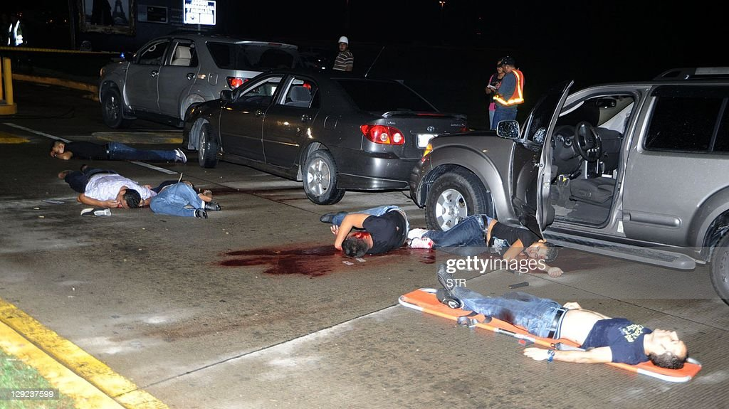 The bodies of six men murdered by suspected gang members lie in the parking lot of Ramon Villeda Morales Airport in San Pedro Sula 240 kms north of...