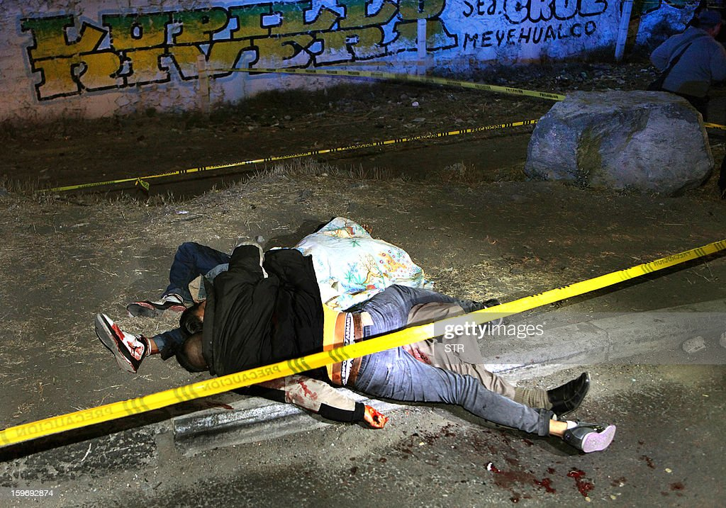 The bodies of three Mexican youngsters lie on Mexico-Puebla highway after being shot by unknown men on January 17, 2013 at the Emiliano Zapata neighborhood in the Municipality of Los Reyes, Mexico state. According to a local newspaper more than thirty people have been killed in the state of Mexico in the past four days.