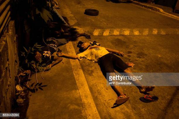 TOPSHOT The bodies of two alleged drug dealers killed during a police antidrug operation lie on the road in Manila on August 17 2017 Police in the...