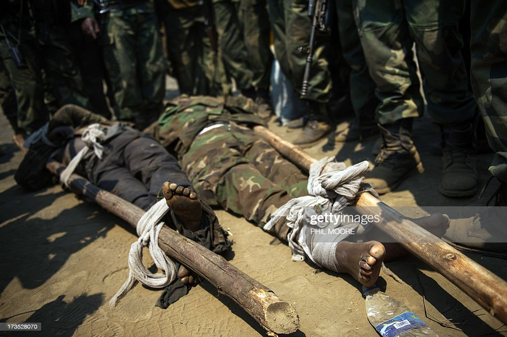 The bodies of two alleged M23 fighters lay on the ground surrounded by Congolese army soldiers in the village of Rusayo during a press visit, some 13km from Goma in the east of the Democratic Republic of the Congo on July 16, 2013. According to the army, one of the men was Ugandan and the other Rwandan, but they could not produce the identity cards that they claimed to have seen proving this. The army in the Democratic Republic of Congo on Tuesday pursued an offensive against rebels of the M23 movement to protect the North Kivu provincial capital of Goma, military sources said. Colonel Mamadou Mbala, head of commando forces in the regular army (FARDC), told AFP by telephone that his troops were ordered to place Goma 'out of danger'. The city is key to a region rich in minerals including gold and coltan, a key component in cell phones and other electronic equipment.