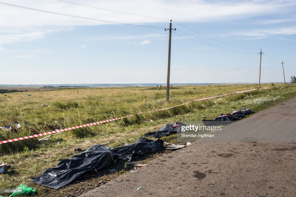 The bodies of victims of the crash of Malaysia Airlines flight MH17 await collection by the side of the road near the crash site on July 20, 2014 in Grabovo, Ukraine. Malaysia Airlines flight MH17 was travelling from Amsterdam to Kuala Lumpur when it crashed killing all 298 on board including 80 children. The aircraft was allegedly shot down by a missile and investigations continue over the perpetrators of the attack.