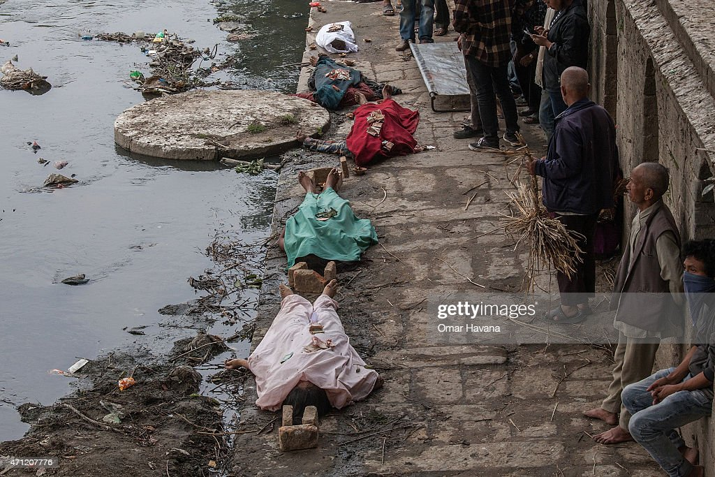 The bodies of victims of the earthquake that hit Nepal yesterday lay on the ground before cremation while relatives stand near by on April 26 2015 in...