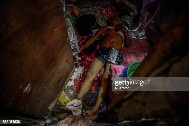 The body an alleged drug user who was killed by unidentified assailants lies inside a house in Quezon city Metro Manila Philippines December 8 2017...