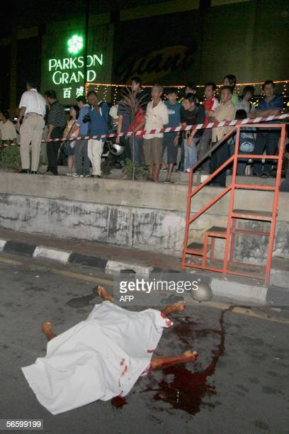 OUT* The body of a bomb explosion victim lies in the street near a shopping complex in Penang state late 15 January 2006 A bomb exploded during an...