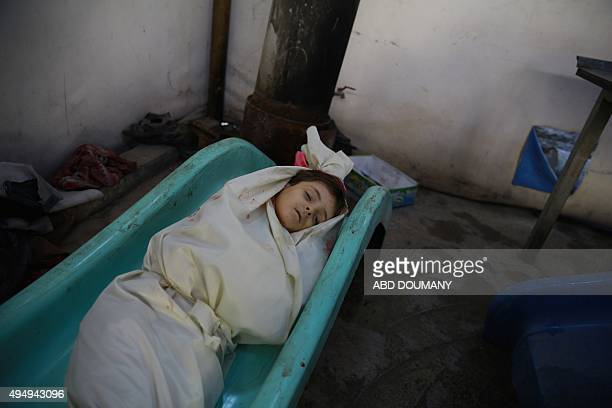 The body of a child wrapped in a shroud waits for identification following a reported airstrike by Syrian government forces on the rebelheld town of...