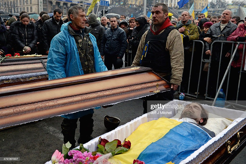 The body of a dead anti-government demonstrator killed in clashes with police is viewed by men dressed in military clothing in Independence square on February 22, 2014 in Kiev, Ukraine. Ukrainian members of parliament have voted to oust Viktor Yanukovych and bring presidential elections forward to the 25th of May.