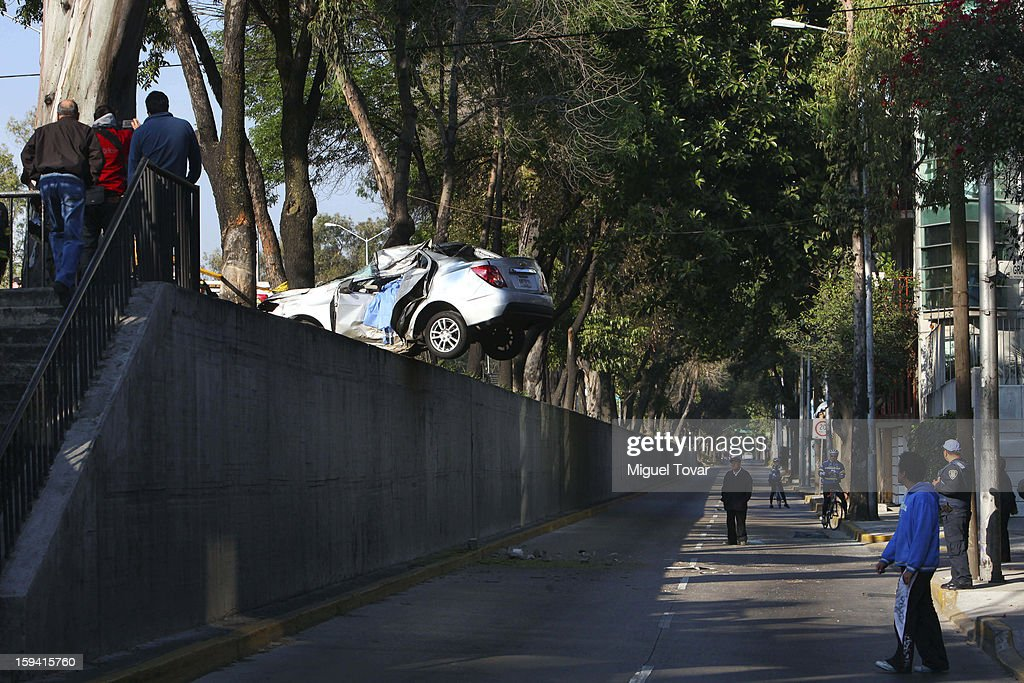The body of a dead woman remains inside her car after crashing on a freeway in Mexico City on January 13, 2013 in Mexico City, Mexico.