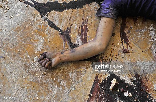 The body of a man believed to be a fighter loyal to the Syrian regime lies at the Umayyad Mosque in the old city of Aleppo hours before the Syrian...