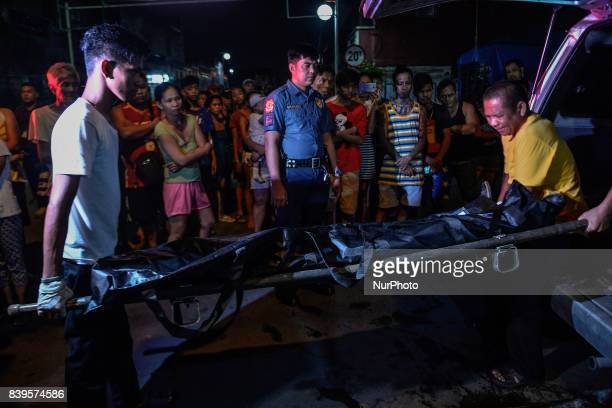 The body of a man is loaded into a funeral van after he was killed by police following a police operation in Manila Philippines August 17 2017 Amidst...