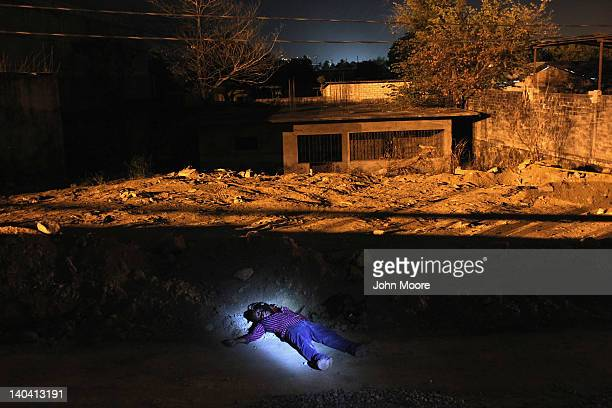 The body of a man killed in a suspected drugrelated execution lies along the path where he was shot on March 1 2012 in Acapulco Mexico Drug violence...