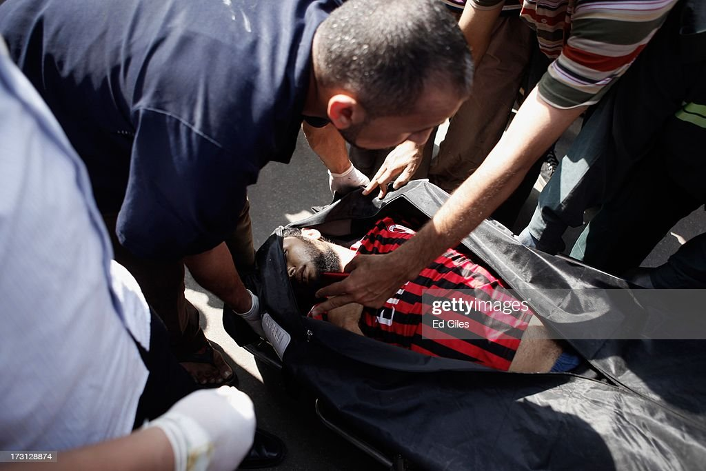 The body of a man lies in a body bag at the Liltaqmeen al-Sahy Hospital in Cairo's Nasr City district, after allegedly being killed during a shooting at the site of a pro-Morsi sit-in in front of the headquarters of the Egyptian Republican Guard on July 8, 2013 in Cairo, Egypt. Egyptian health ministry officials are reporting at least 42 people were killed and more than 300 injured in the incident early on Monday morning, which allegedly occurred as supporters of deposed Egyptian President Mohammed Morsi attending the sit in were performing dawn prayer. The demonstrators were demanding the release of Morsi, who they believe is being held inside the Republican Guard headquarters.