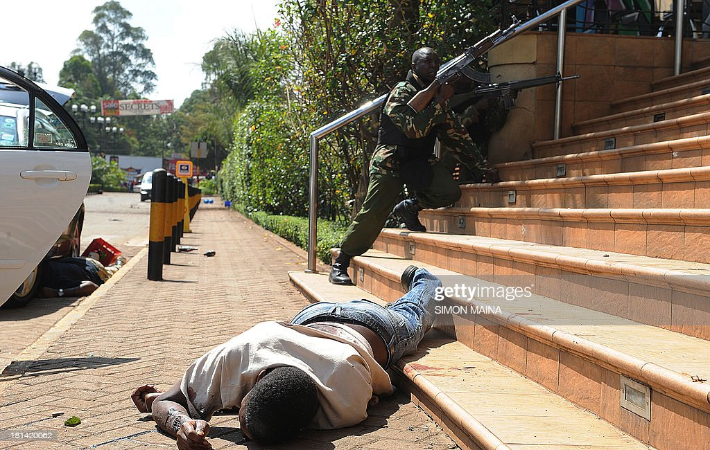 The body of a man lies on the ground as armed policemen try to get entry into the Westgate after masked gunmen stormed an upmarket mall and sprayed gunfire on shoppers and staff, killing at least six on September 21, 2013 in Nairobi. The Gunmen have taken at least seven hostages, police and security guards told an AFP reporter at the scene.