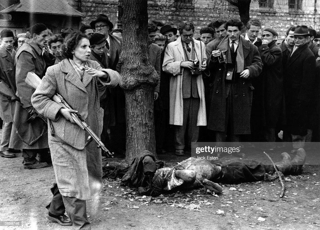 The body of a member of the Hungarian secret police lies in a Budapest street as western journalists witness the anti-communist uprising in Hungary. Even teenagers and women took arms against the communist state, summarily executing those suspected of involvement with the state's secret police (AVH or AVO). Amongst the crowd with his camera is photographer John Sadhovy (with mustache). Original Publication: Picture Post - 8730 - Hungary's Last Battle For Freedom - pub. 1956