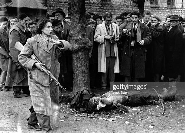 The body of a member of the Hungarian secret police lies in a Budapest street as western journalists witness the anticommunist uprising in Hungary...