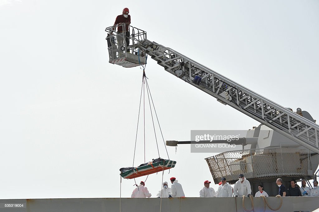 The body of a migrant is evacuated from Italian Navy ship 'Vega' which transports more than 600 migrants rescued at sea and the bodies of 45 people, on May 29, 2016 in the port of Reggio Calabria, southern Italy. A week of shipwrecks and death in the Mediterranean culminated today with harrowing testimony from migrant survivors who said another 500 people including 40 children had drowned, bringing the number of feared dead to 700. / AFP / GIOVANNI