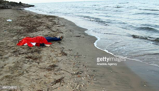 The body of a migrant is washed ashore on a beach after a boat carrying 12 migrants sank off the coast of Mugla's Bodrum district Turkey on September...