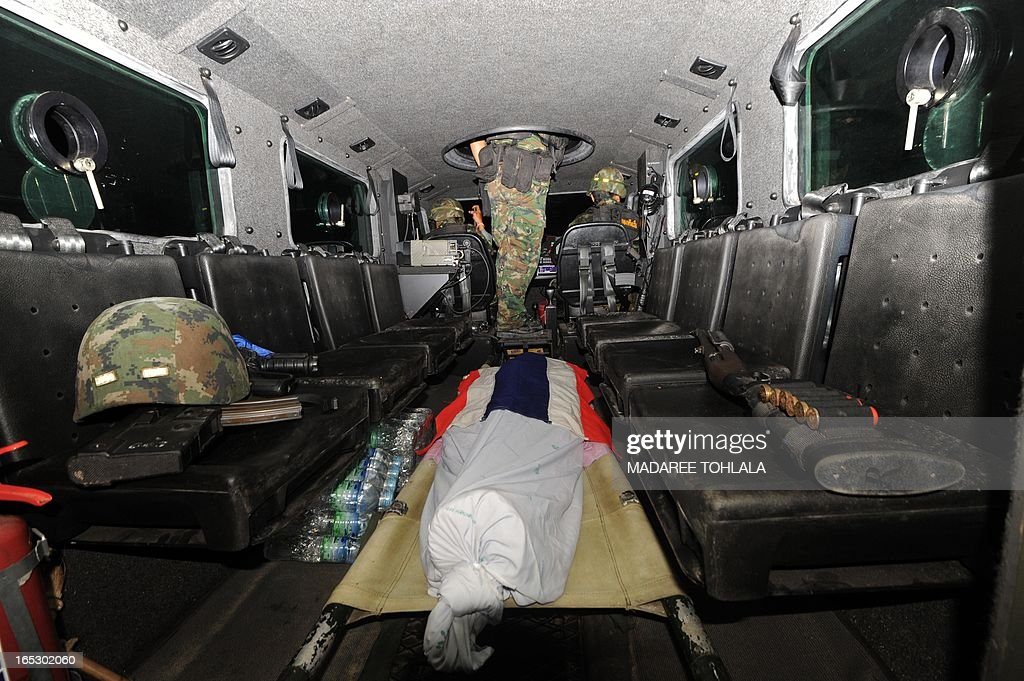 The body of a Muslim soldier who was killed by suspected separatist militants lies on a stretcher inside a Thai amy armoured vehicule as i drives to a hospital in Thailand's restive southern province of Narathiwat on April 2, 2013. Muslim Thai private marine who was abducted from his house two days ago found shot dead in appraently retaliation by militants from their massive loss last month, Thai army said. AFP PHOTO/ Madree Tohlala