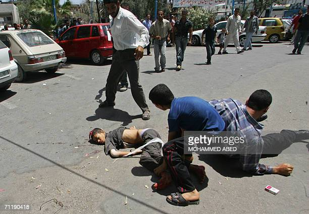 The body of a Palestinian boy killed in an Israeli air raid 13 June 2006 lies on the ground outside a hospital in Gaza City after the man carrying...