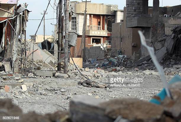 The body of a reported jihadist fighter lies amidst debris on December 27 2015 in the Hoz neighbourhood in central Ramadi the capital of Iraq's Anbar...