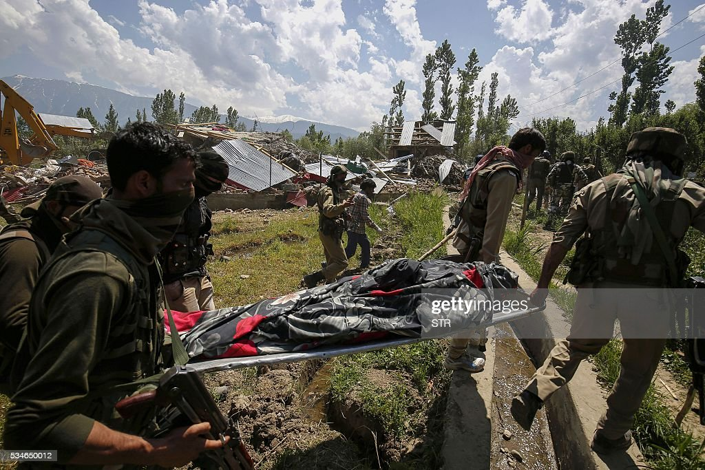 The body of a suspected militant is carried on a stretcher after a gunbattle with Indian soldiers in Kotchipora village near Tangmarg in north Kashmir's Baramulla district on May 27, 2016. Indian troops shot dead two suspected militants and destroyed one house during a gunbattle in the restive region. / AFP / STR