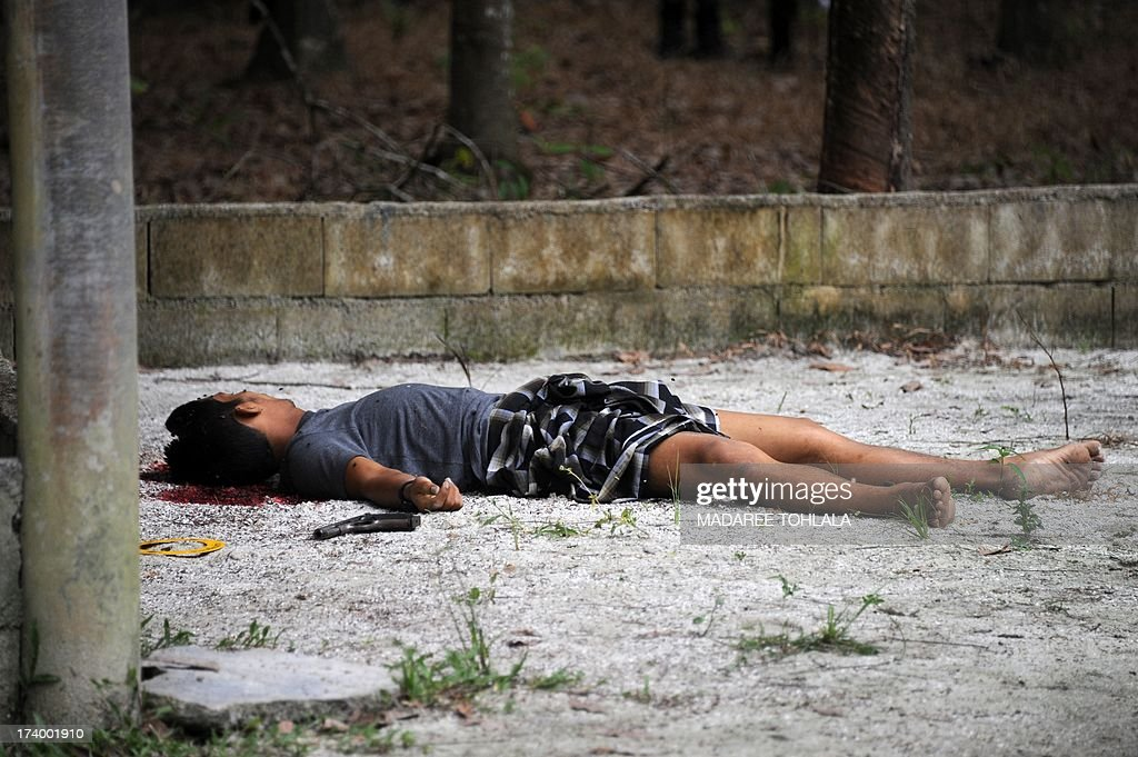The body of a suspected separatist militant who was shot dead during a clash with Thai army Rangers lay on the ground in the Cho-i-rong district of Thailand's restive southern province of Narathiwat on on July 19, 2013. A nine-year-old insurgency has claimed more than 5,500 lives in the Muslim-dominated south, where many local people complain of a long history of discrimination by Thai authorities in the Buddhist-majority nation. AFP PHOTO/Madaree Tohlala